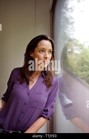 Thoughtful woman looking through window while leaning against wall at home - Stock Photo