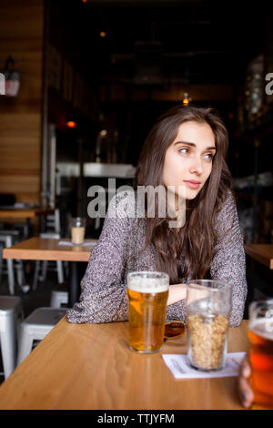 Thoughtful woman having beer while sitting at table in brewery - Stock Photo