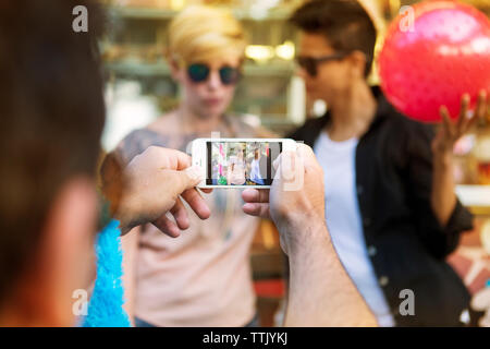 Man photographing female friends through smart phone at amusement park - Stock Photo