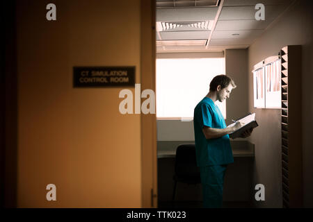 Doctor reading reports while standing in hospital ward - Stock Photo
