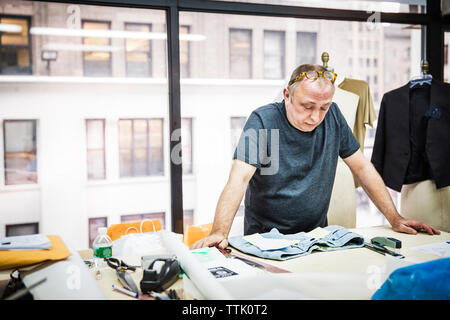 Serious fashion designer looking at jeans on table against glass window in design studio - Stock Photo