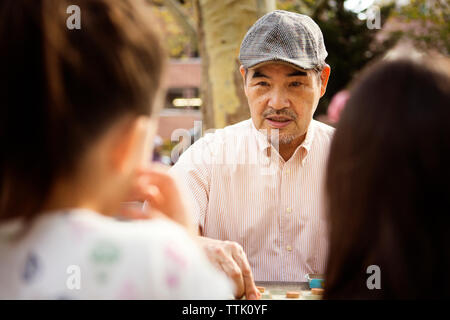 Grandfather playing checkers game while sitting at table in park - Stock Photo