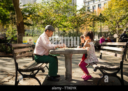 Side view of grandfather and granddaughters playing game while sitting on bench in park - Stock Photo