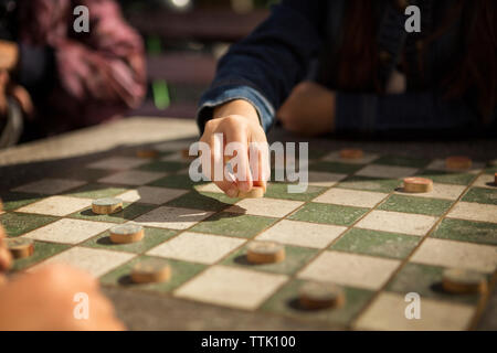 Cropped image of girls playing checkers game - Stock Photo