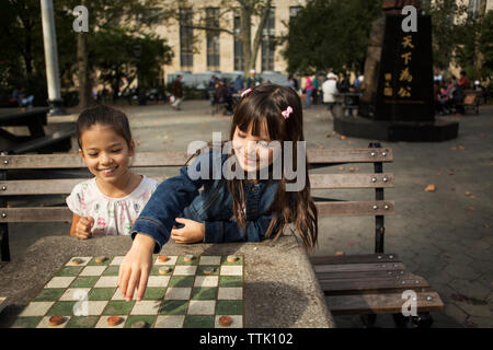 Smiling sisters playing checkers game in park - Stock Photo