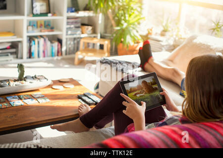 Girl looking at pictures in tablet computer while sitting on sofa - Stock Photo