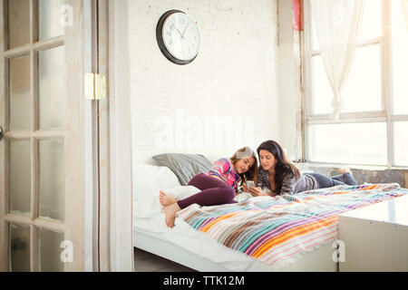 Mother and daughter looking at smart phone while relaxing on bed - Stock Photo
