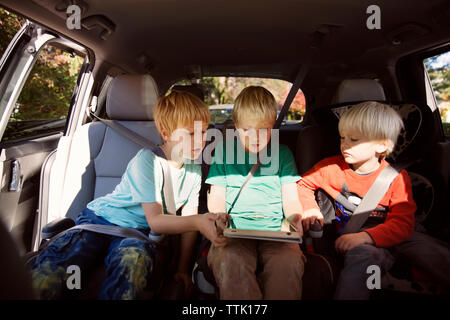 Brothers looking at tablet computer while sitting in car - Stock Photo