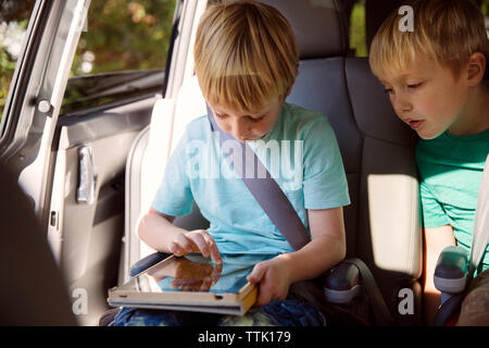 Boy using tablet computer while sitting in car - Stock Photo