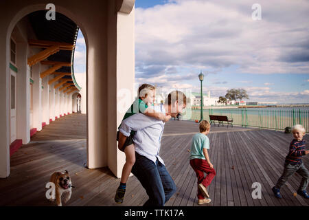 Playful family on boardwalk outside building against cloudy sky - Stock Photo
