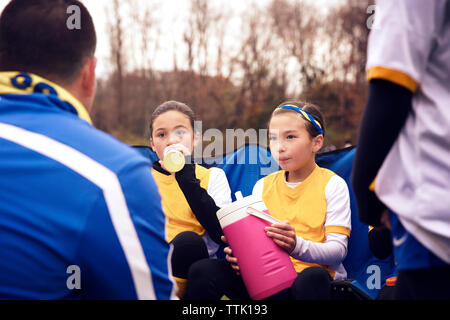 Soccer players listening to coach while drinking water during match - Stock Photo