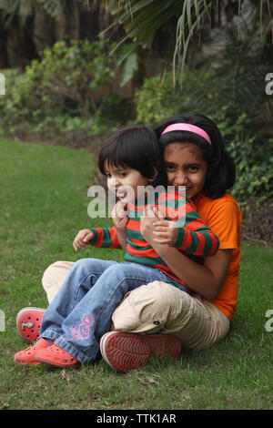 Two Indian girls playing in a lawn - Stock Photo