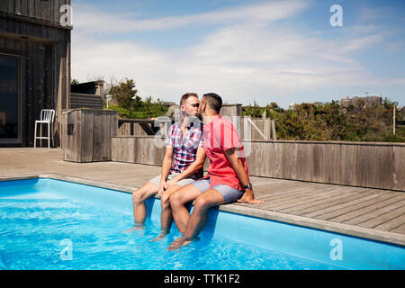 Homosexual couple kissing while sitting on poolside against sky - Stock Photo