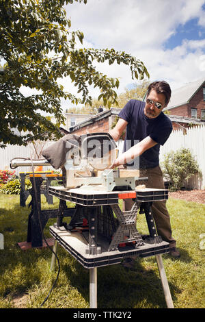 Man cutting wood at table saw while standing in yard - Stock Photo