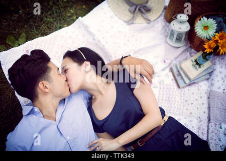 Overhead view of couple kissing while lying on field at park - Stock Photo