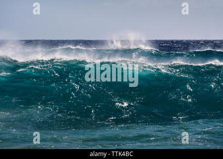 Scenic view of sea waves splashing against clear sky - Stock Photo