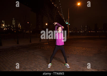 Thoughtful young woman stretching while standing on street against Manhattan Bridge at night - Stock Photo