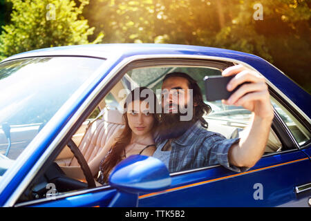 Couple taking selfie while sitting in pick-up truck - Stock Photo