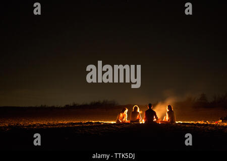 Friends sitting around bonfire at beach during night - Stock Photo