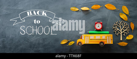 Back to school concept. Top view banner of school bus, alarm clock and pencil next to tree with autumn dry leaves over classroom blackboard background - Stock Photo