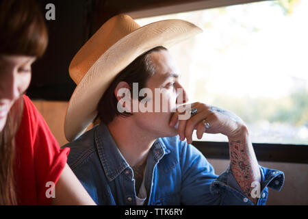 Close-up of thoughtful man traveling in camper van with woman - Stock Photo
