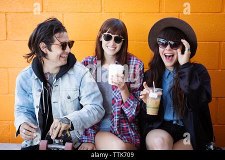 Cheerful friends sitting on retaining wall - Stock Photo