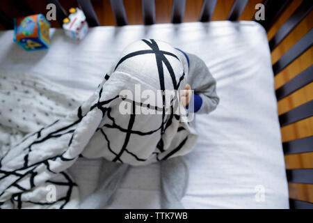 Overhead view of playful baby boy hiding in blanket while playing peekaboo in crib at home - Stock Photo