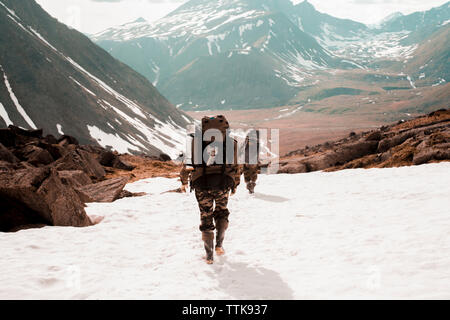 Rear view of hikers with backpacks walking on mountain during winter - Stock Photo