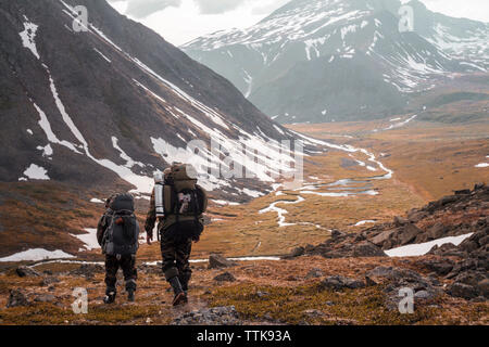 Rear view of hikers with backpacks walking on landscape during winter - Stock Photo