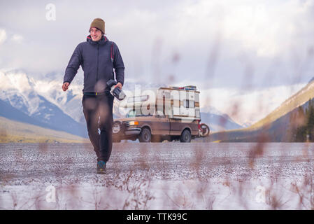 Man walking toward camera next to Camper Truck with Touring Motorcycle - Stock Photo