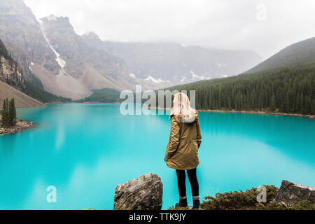 Rear view of female hiker with hand in pocket standing by Moraine Lake against mountains at Banff National Park - Stock Photo