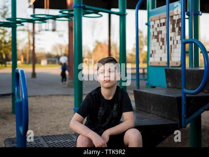 Sad boy looking away while sitting at playground - Stock Photo