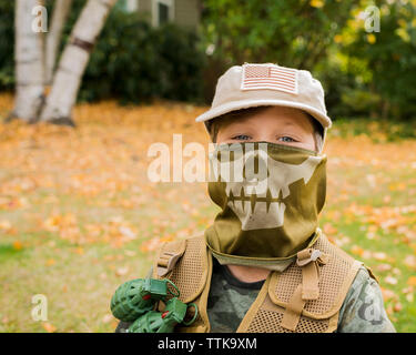 Portrait of cute boy wearing army soldier costume while standing on grassy field in park - Stock Photo