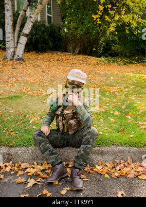 Portrait of boy wearing army soldier costume while sitting on grassy field in park - Stock Photo