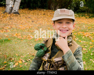 Portrait of cute smiling boy wearing army soldier costume while sitting on grassy field in park - Stock Photo