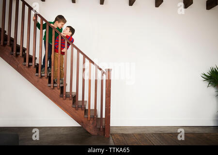 Brothers playing on wooden staircase at home - Stock Photo