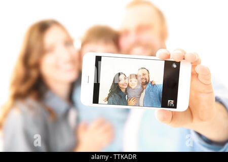 Happy family taking photo of themselves isolated on white - Stock Photo