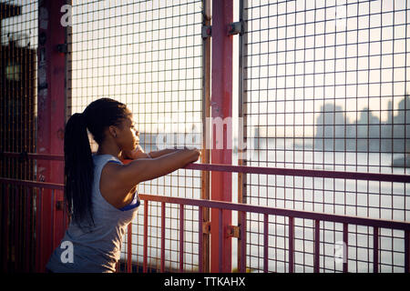 Thoughtful young woman standing by fence on sunny day - Stock Photo