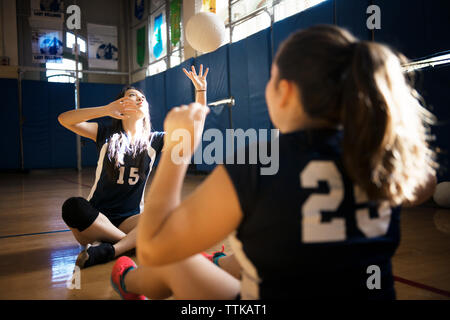 Girls playing catch with volleyball on floor - Stock Photo