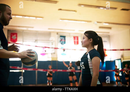 Male coach holding ball and talking on girl at volleyball court - Stock Photo