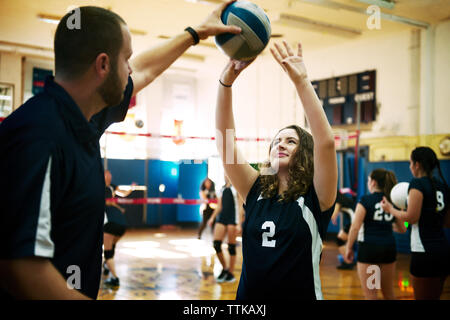 Male coach teaching girl in volleyball court - Stock Photo