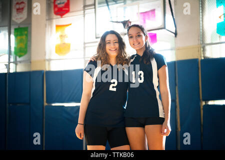 Portrait of smiling teenage girls standing in volleyball court - Stock Photo