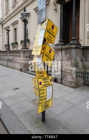 A street post in London W1 with parking restriction notices all over it - Stock Photo