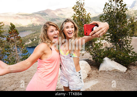 Happy female friends taking selfie with mobile phone while standing on mountain in forest - Stock Photo