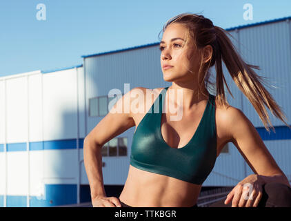 Thoughtful young woman wearing sports bra while standing against buildings in city - Stock Photo