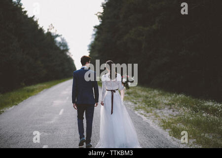 Rear view of bride and groom walking on road amidst trees - Stock Photo