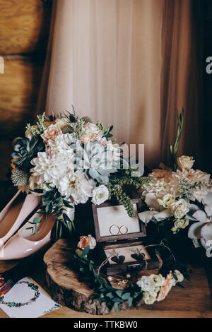 High angle view of wedding rings amidst wreath by bouquet on table