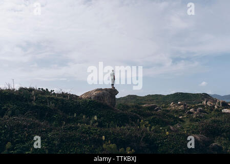 Mid distance view of man standing on rock against cloudy sky - Stock Photo