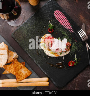 High angle view of beef tartare with pickled cucumber and fresh onion on slate - Stock Photo