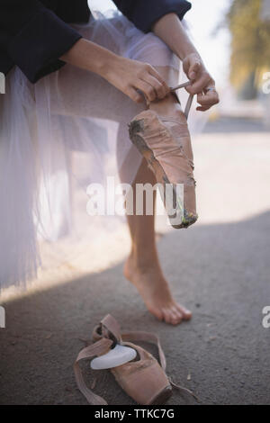 Low section of ballerina wearing torn ballet shoes on road in city - Stock Photo
